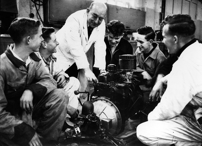 1957 — Staff and students of Seddon Memorial Technical College examine the features of a new internal combustion engine, presented to them by the Auckland Garage Proprietors' Association.